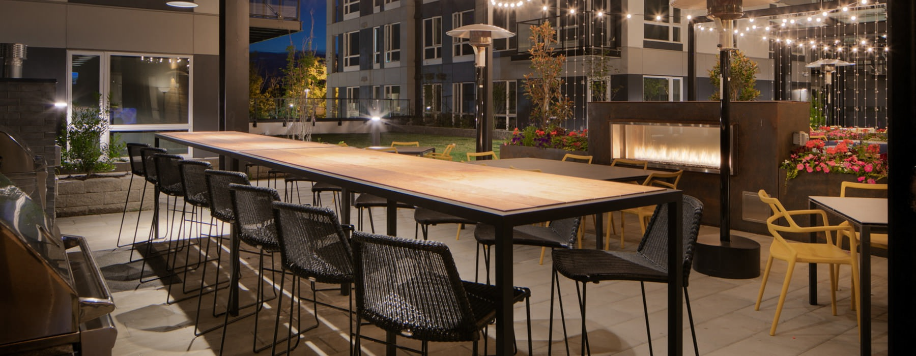 outdoor patio grilling area with long table and chairs in front of fireplace